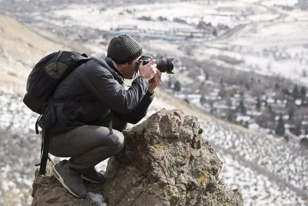 A beginner photographer looking through his viewfinder towards the mountains.