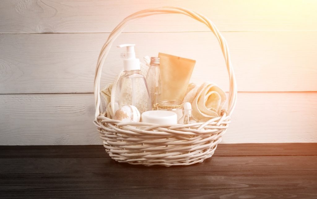 Wicker basket with spa treatments on wooden table.