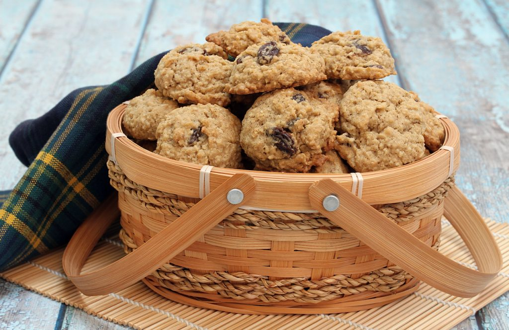 Homemade oatmeal raisin cookies in a basket on a blue rustic table.