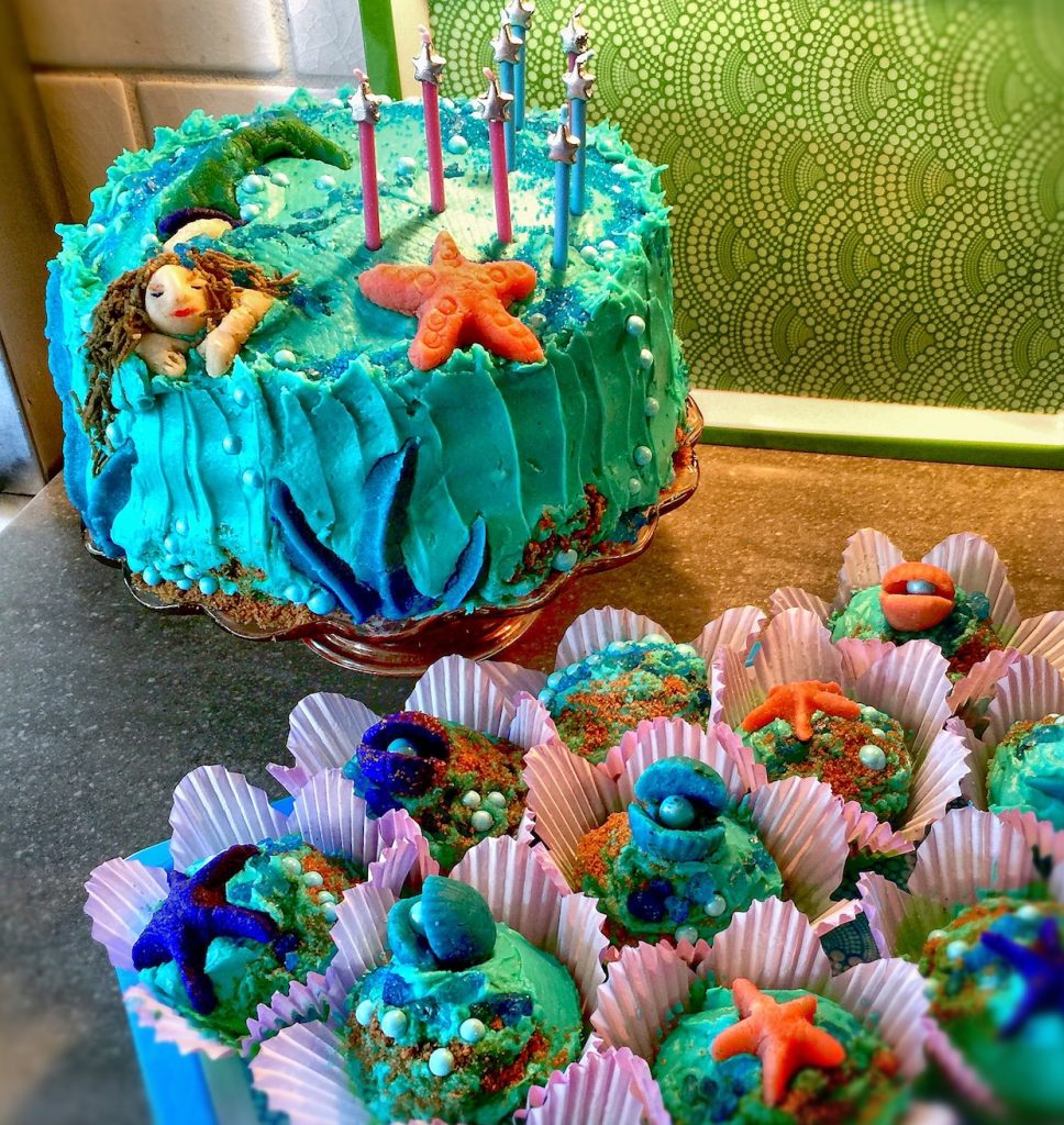 Mermaid birthday cake in aqua, blue, green, and purple.