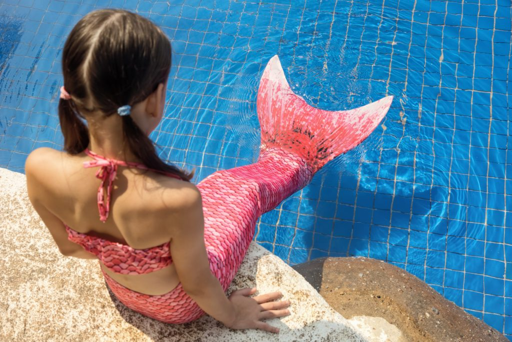 Mermaid girl with pink tail on rock at poolside put feet in water.
