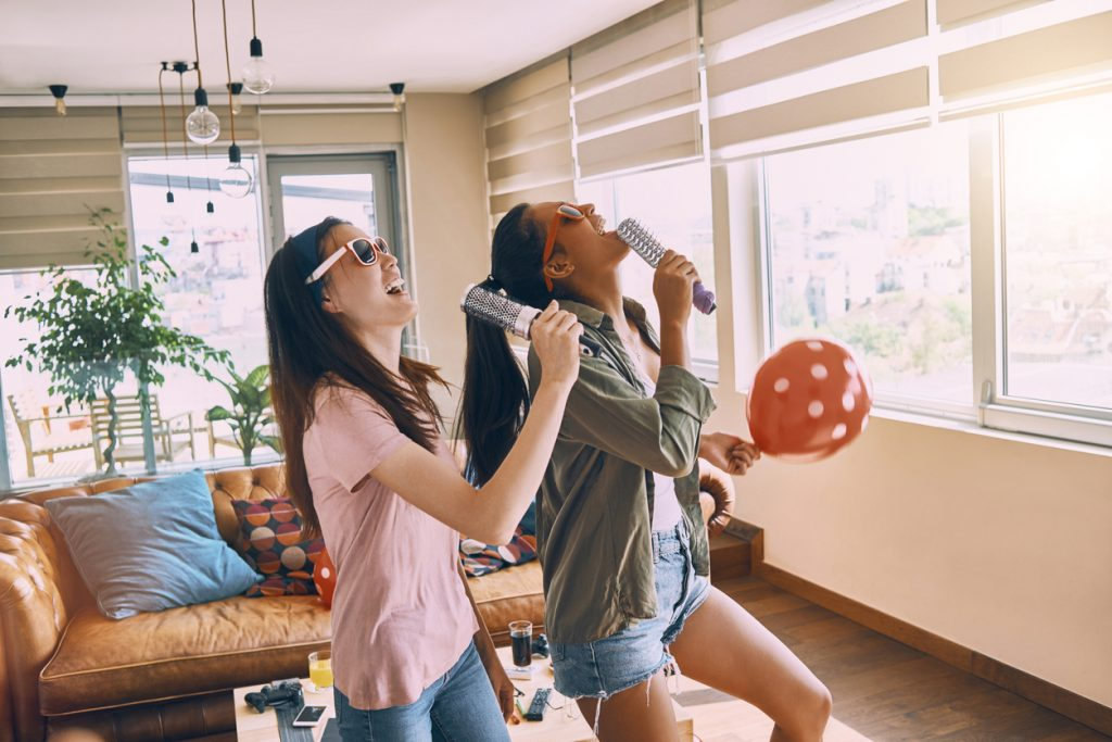 two cheerful friends singing and having fun