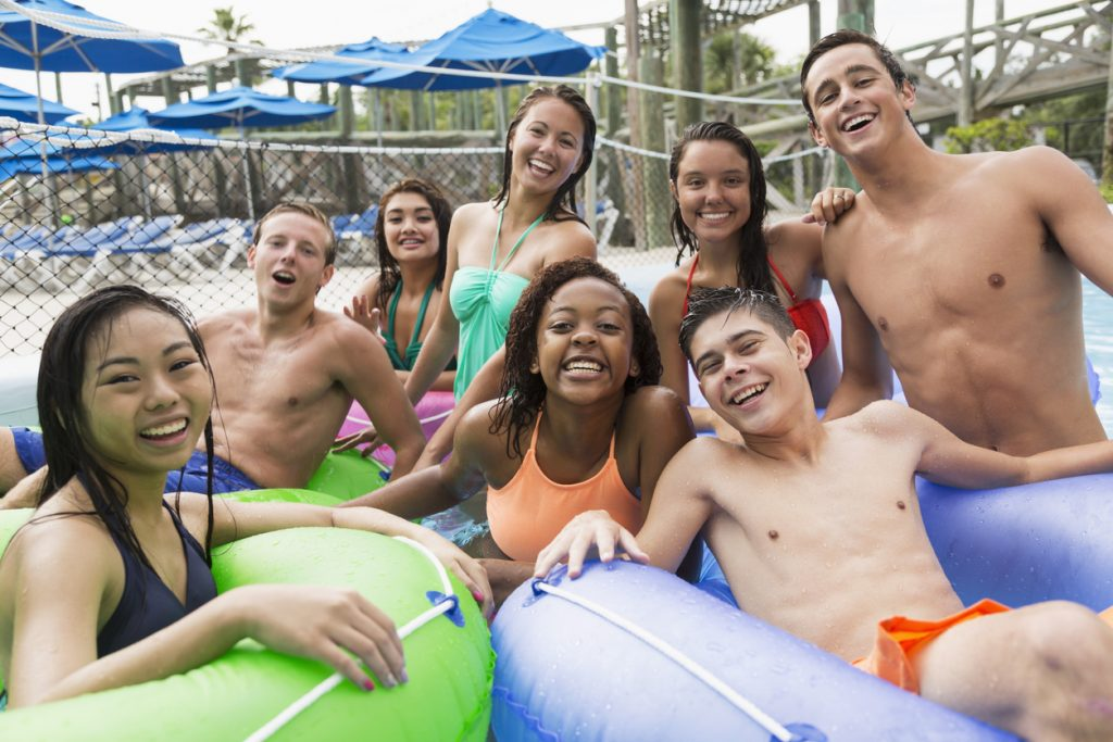 group of teens floating on inflatable rings at a water park.