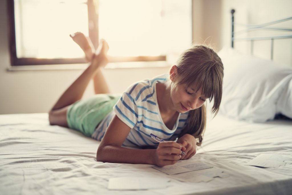 Teenage girl lying on bed and writing her kids thank you notes.